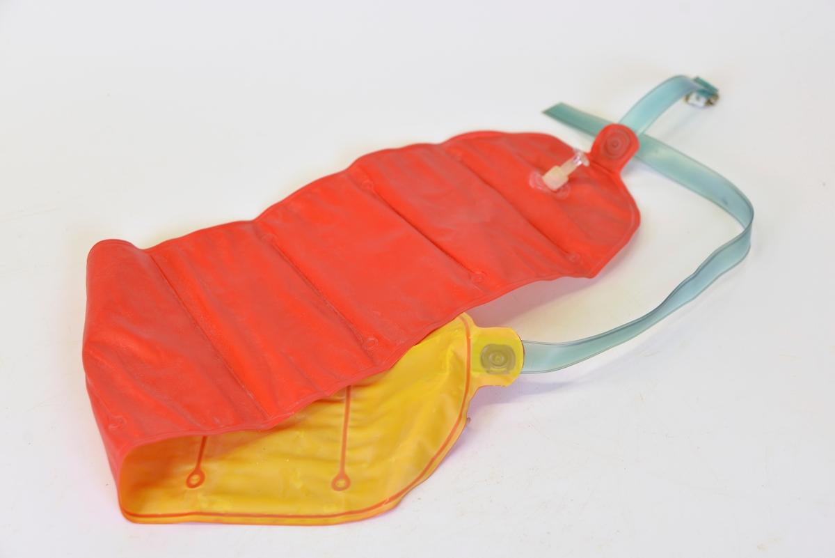 Uppblåsbar simdyna med band med spänne. Röd ovansida, gul insida.