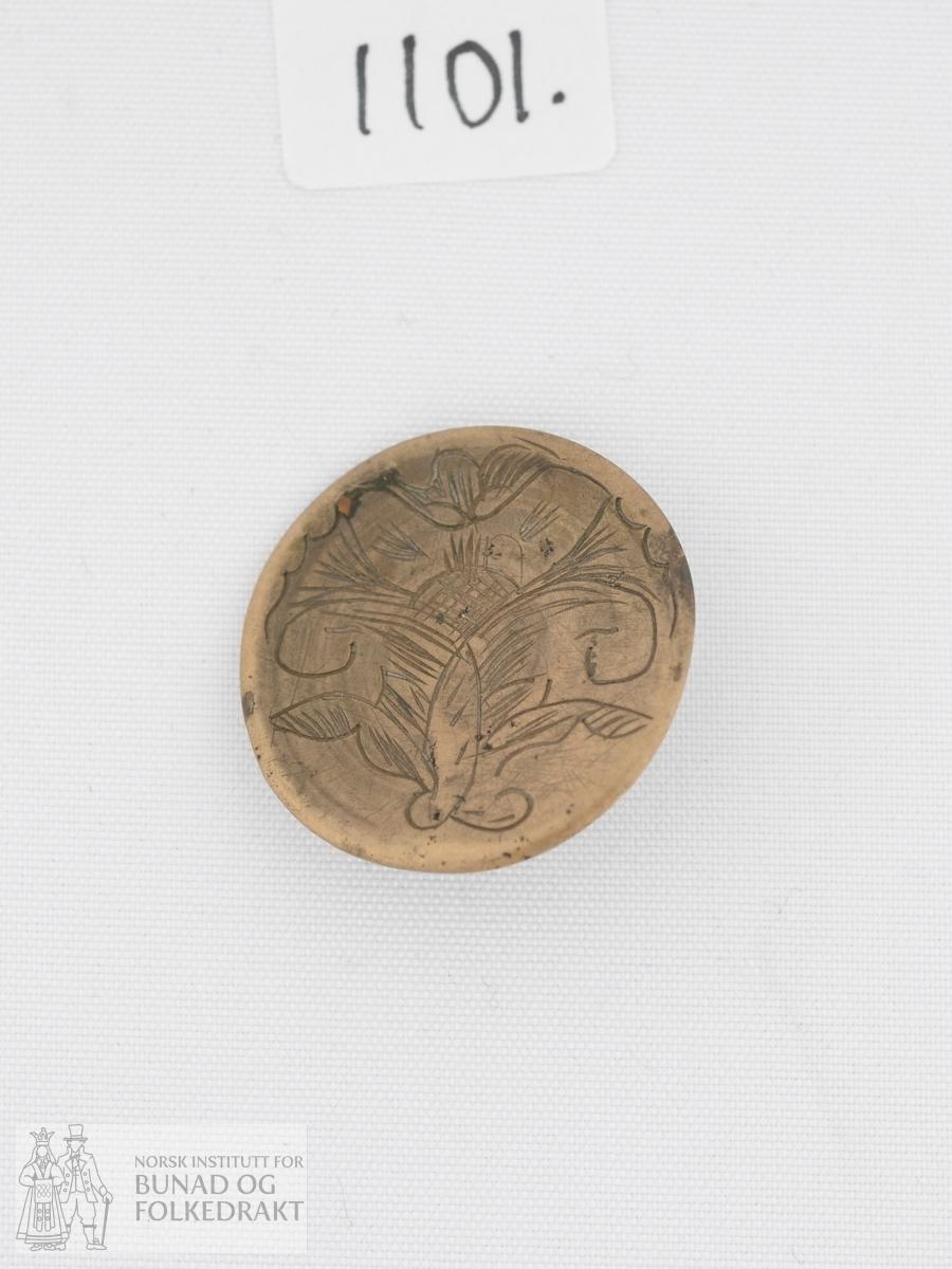 Knapp stansa ut av ei messingplate og pålodda krok på baksida. Pryda med ein gravert og noko stilisert akantusblome som dekker heile knappen.