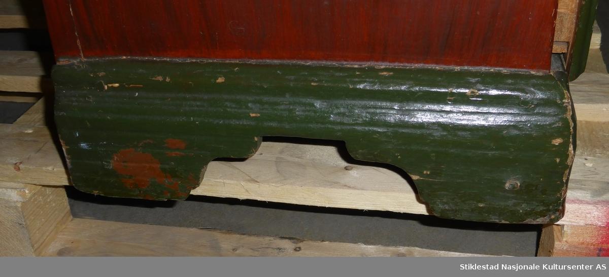 Skatoll med 4 skuffer, hvorav den øverste er i mindre format. De 3 nederste skuffene har uthevet speilfelt, formet som en skråstilt firkant med høvlet horisontale spor. Minste og øverste skuff har rektangulært speilfelt med samme type dekor. Skatollets klaff har to rektangulære speilfelt med dekormaling. Innvendig er skapet ådringsmalt.  Skapet er monter på fotlist/sokkel som har høvlet horisontale spor. Forholdsvis lite skatoll. Skapet er sinket og naglet sammen (smiddspiker og tre nagler). Innvendig er skapet inndelt i 7 rom med en skuff (skal ant være to skuffer).  Skapet har (antatt) sekundær maling både utvendig og innvendig som har begynt å flasse av i større flak.  Nyere hengsler påmontert, låskasse defekt.