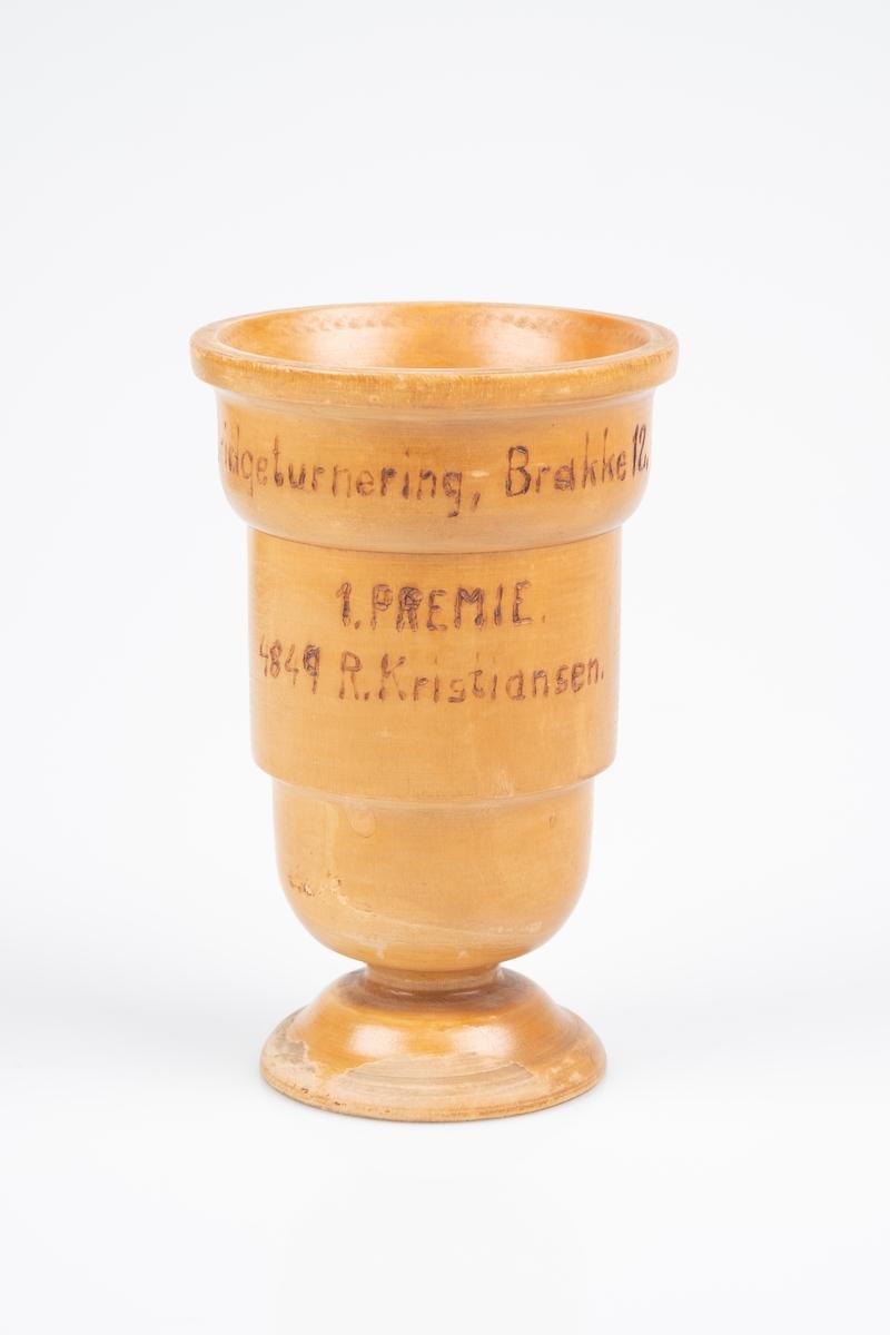 En pokal i tre. Pokalen er dreid og har innbrent tekst.