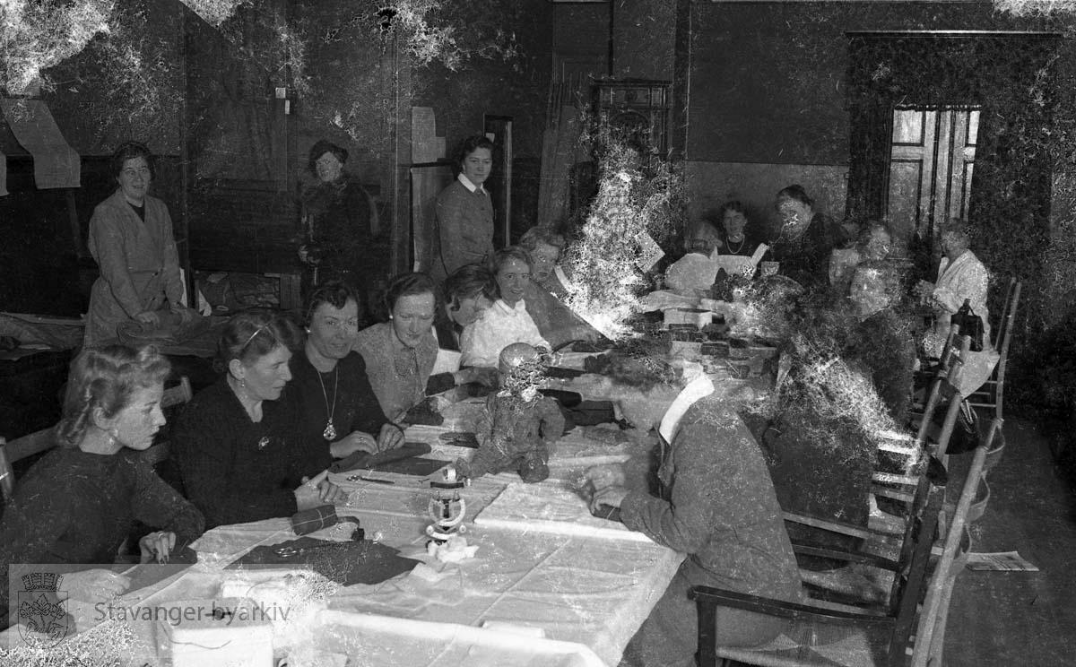 Kvinner med sysaker og førstehjelpsutstyr samlet rundt bordet.