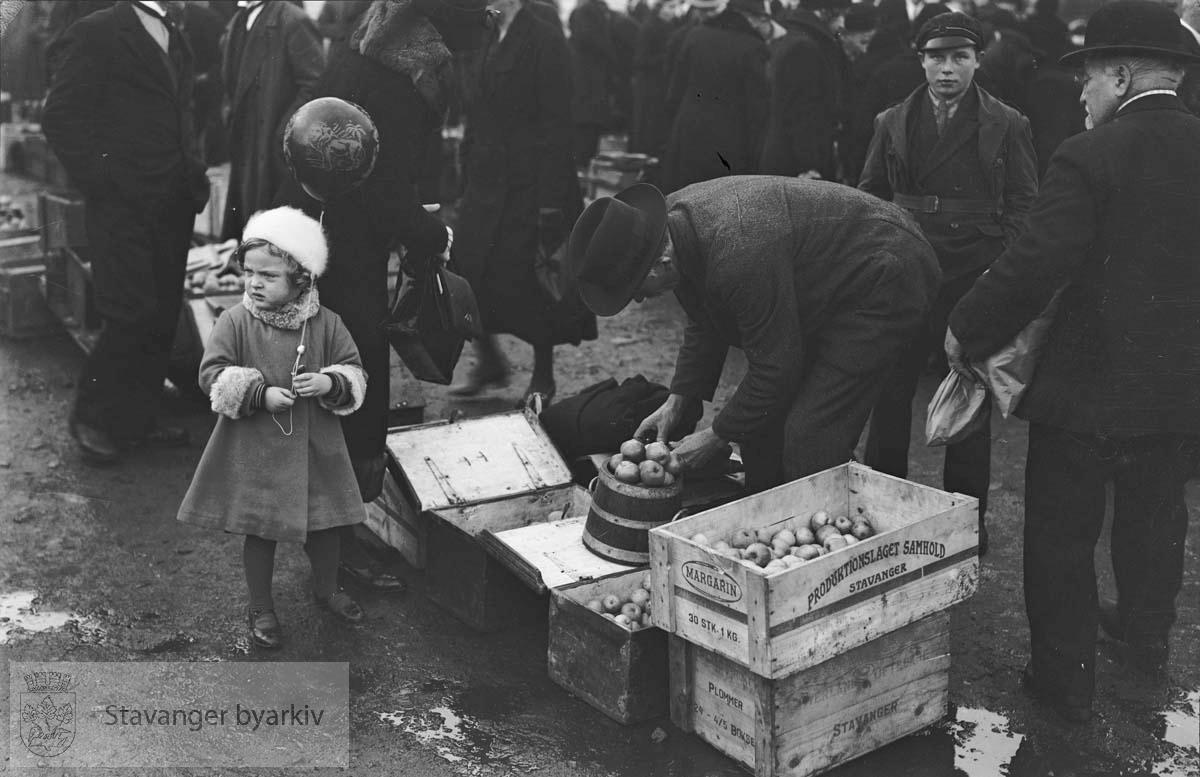 Marked på torget.Epler i kasser. Jente med ballong