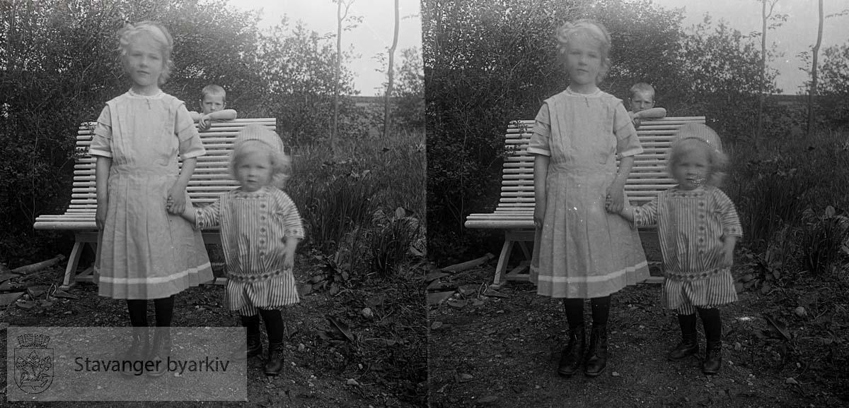 Borghild og Christian Eckhoff i hagen. Bak benken står en gutt og lurer...Stereofotografi..