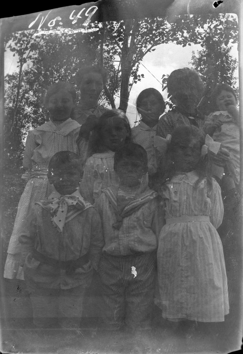Gruppeportrett av tre kvinner og seks barn, fotografert utendørs.