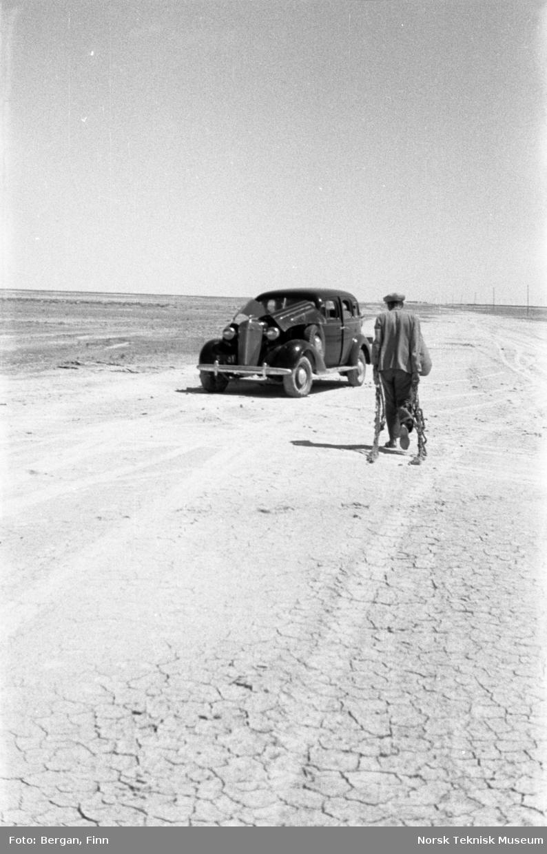Bil som har kjørt seg fast, men kommet løs fra ørkensand. Person som trekker med seg kjetting el.