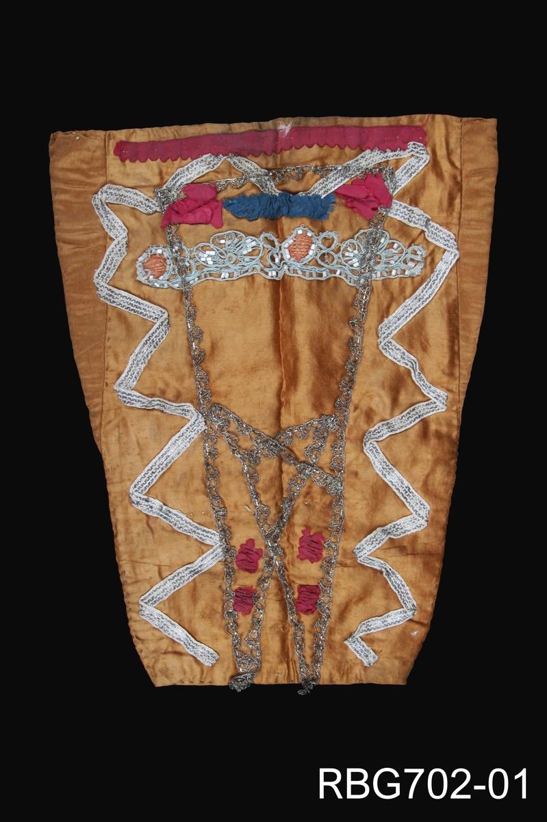 Håndsydd dåpssmekke med metallknipling som danner et mønster. Videre er røde silkerosetter, tilklipte silkebiter og et fint blondestykke med perlemorsfarga, kantete perler sydde på framsiden. Smekka har en trapesform noe som er vanlig for Rogalandssmekkene. På baksiden er det blitt brukt ubleika kattun som er påtrykt brunt blomstermotiv.