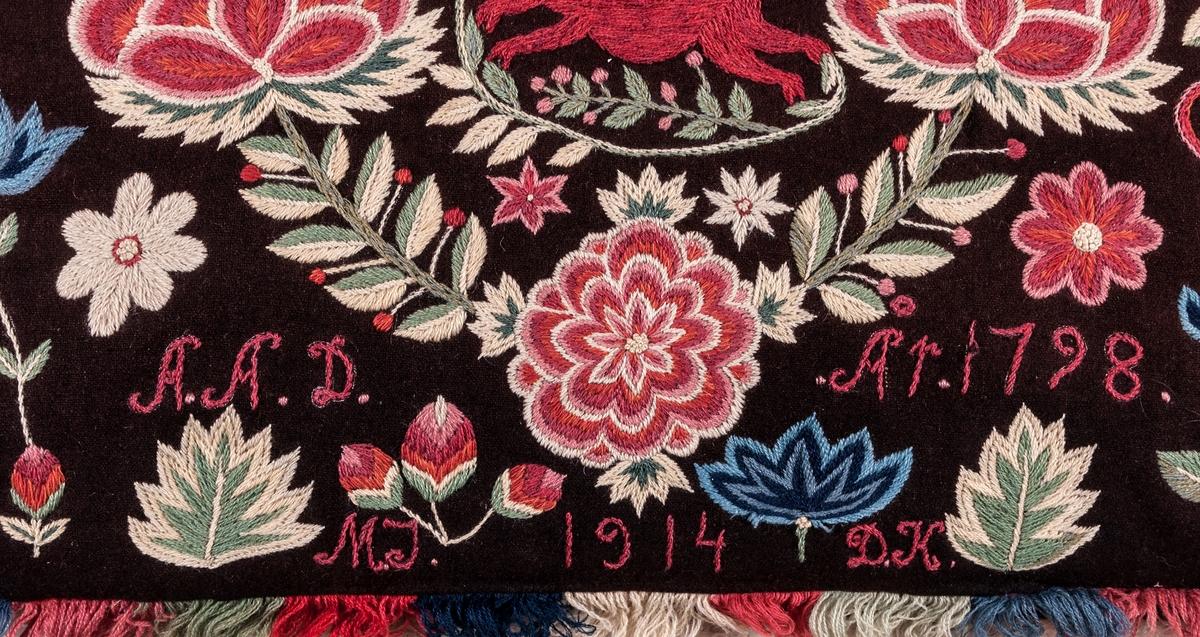 Åkdyna från Skåne, (agedyna), På brun vadmal broderi i ullgarn i starka färger. Inom en krans en löpande hjort. På sidorna vaser med blommor. Fodrad med röd vadmal, kantad med mångfärgad kavelfrans. Schattérsöm och något stjälksöm.  Sign. A A D. År 1798. Nedtill insytt M J 1914 D K.  Kopierad vid Malmöhus läns hemslöjd 1914 till Baltiska utställningen samma år - efter ett original från 1798.