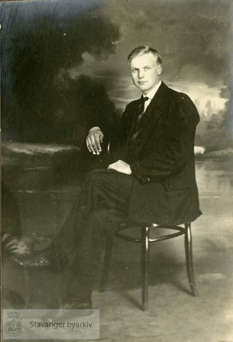 Portrett av ung mann i dress, med landskapsbakgrunn