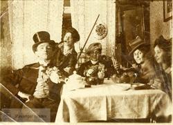 Mann i flosshatt og fire damer rundt et bord
