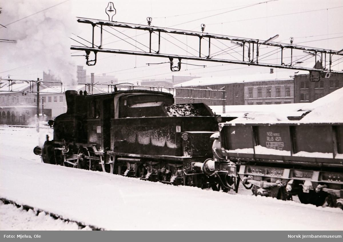 Damplokomotiv type 21b nr. 372 på Oslo Østbanestasjon med sidetippvogner lastet med snø.