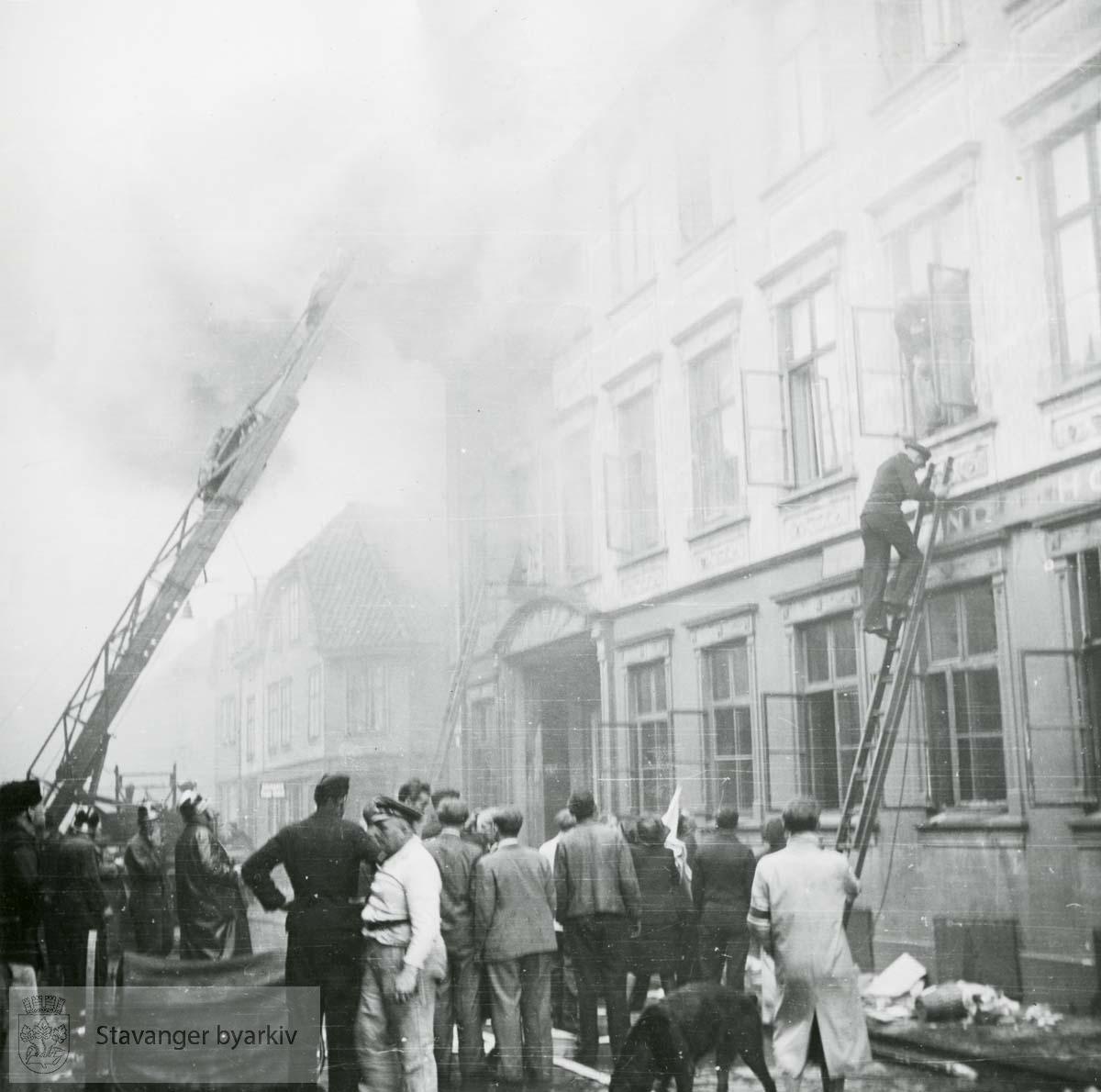 Brannmenn bruker stiger i slukkingsarbeidet. .Grand hotel var en 3 etasjers trebygning reist av skipsreder Søren Berner etter bybrannen i 1860. Privatboligen ble ombygd til hotelldrift i 1887. Etter invasjonen 9. april 1940 rekvirerte den tyske okkupajonsmakten hotellet. 9. mai 1945 ble bygningen antent og totalskadd.