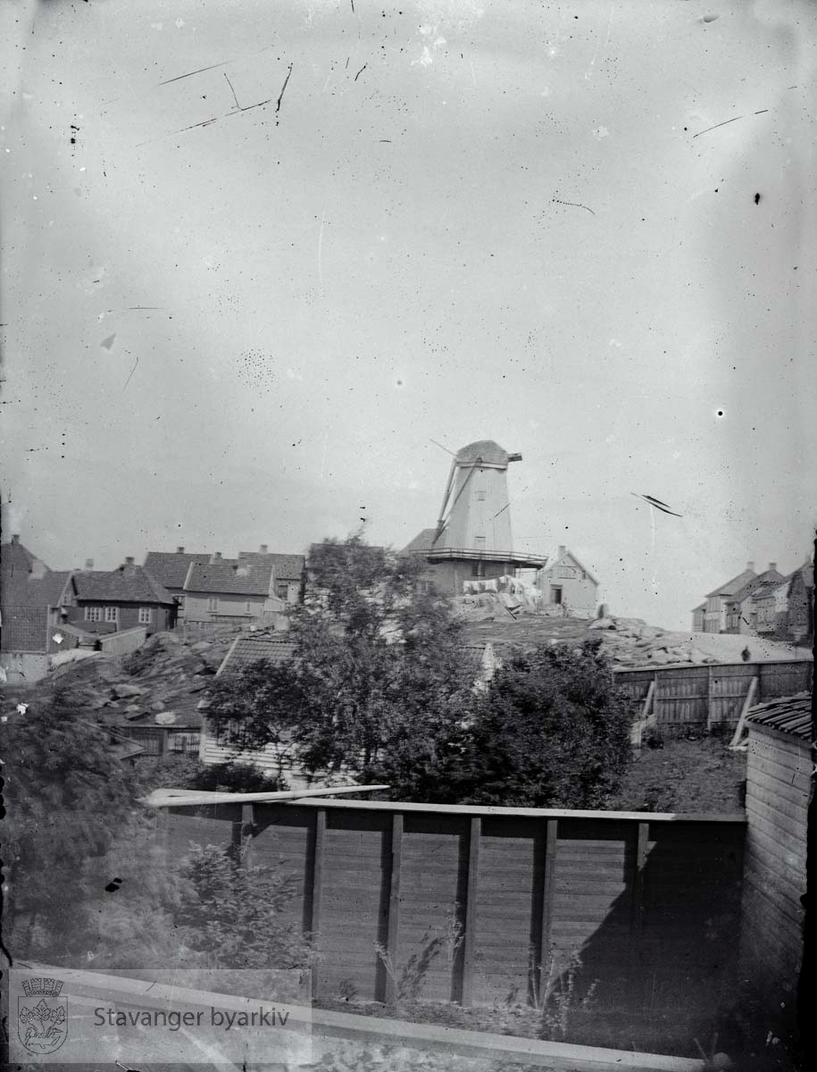 Til høyre Pedersgata mot øst. .Vindmøllen ble oppført i 1836 av Ole Baade og Hans Gabriel Sundt. Den stod opprinnelig i Bergen, men ble demontert og flyttet til Stavanger. Den ble seinere overtatt av firmaet J.A. Köhler & co. Etter å ha malt korn i mange år ble den benyttet som barkemølle med hester som drivkraft. Den malte barken ble brukt i garveriene. Vindmølla ble revet et stykke ut på 1950-tallet, men da hadde den vært ute av drift i lang tid allerede.