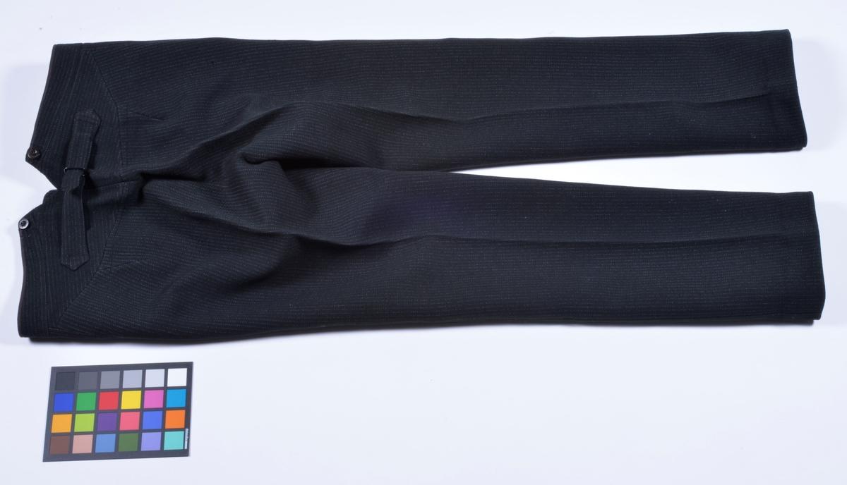 Jaquetten är en högtidsdräkt för dagtid. Just denna jaquette är tillverkad omkring år 1900 för godsägare Axel Dickson, Vikaryd, Alingsås. Det blå bandet representerar hans engagemang i nykterhetsrörelsen. Tiden reflekteras i att rocken har både servettficka och urficka.