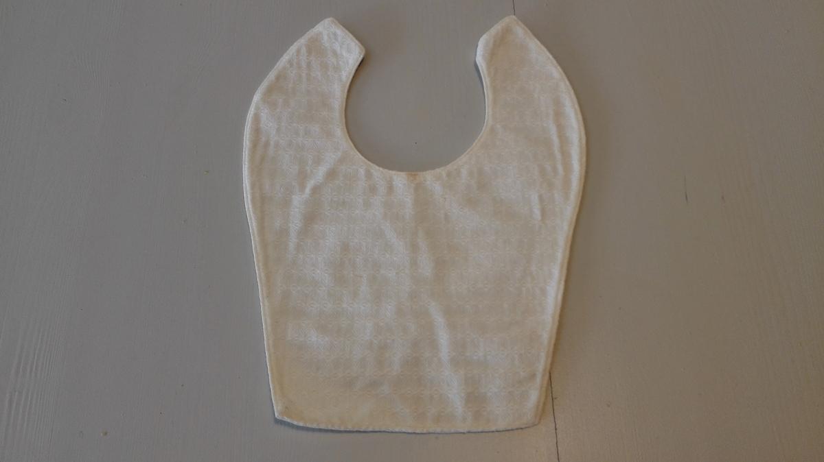 Form: Klypt i eit stykke. med utringing for hals. Heilfora. Stikningar langs kantane. Brukt av gjevaren og bror hans som barn.