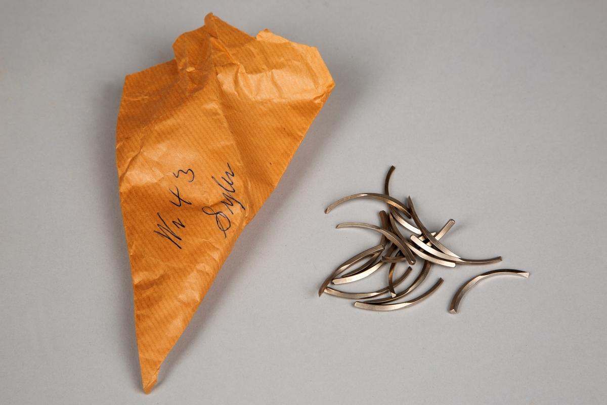 Spisspose med 15 syler for symaskin (?) Buet. Måler 4 cm