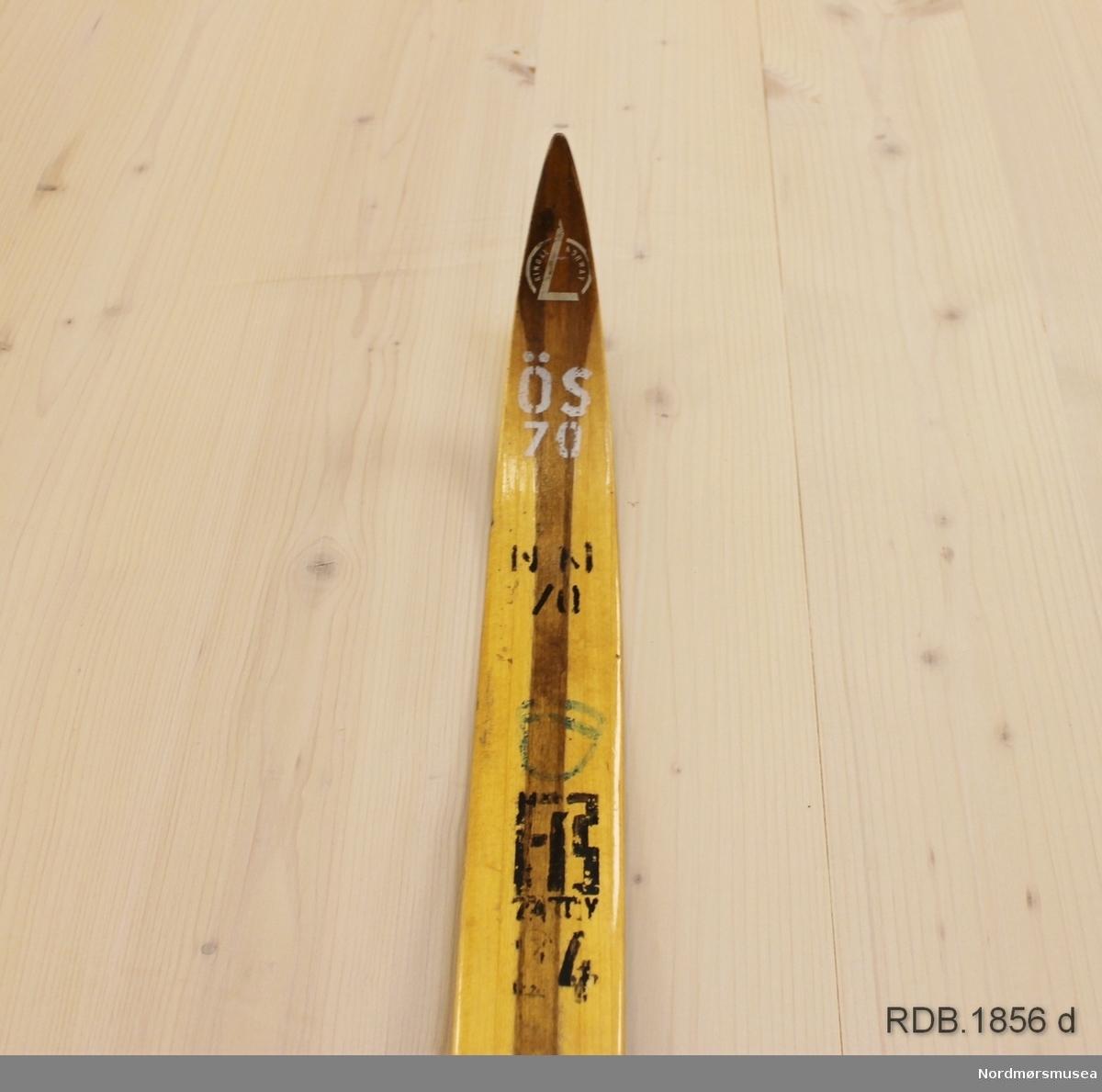 Tilnærmet jevnbred ski med svært liten bue. Bøy uten tupp. Svakt avfaset bakende med litt oppbøy. Dekorert med ei brun stripe på trehvit bunn.  Stempel og klistremerker fra 1970-sesongen på skiet.