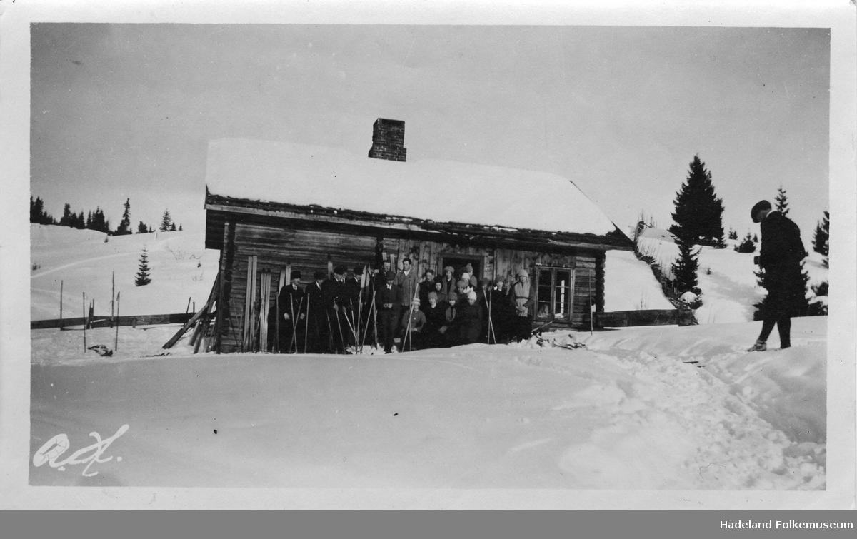En gruppe ungdom og voksne med ski samlet utenfor ei tømmerstue eller hytte. Fotograf til høyre.