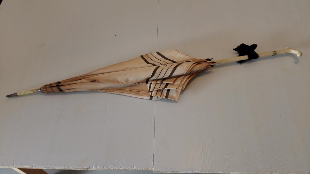 """1 dameparaply.  Dameparaply, kvitt trekk med 4 svarte striper ved kanten og toppen, metalspilar, skaft og handtak av trevyrke som er måla kvitt. Kring skaftet er festa ein """"oren"""" av blankt metal og over denne er knytt ei svart sløyfa. Metaldobbsko. Lengd 93,5 cm. Kjem frå fam. Meidell, Balestrand.  Svein L. Vold"""