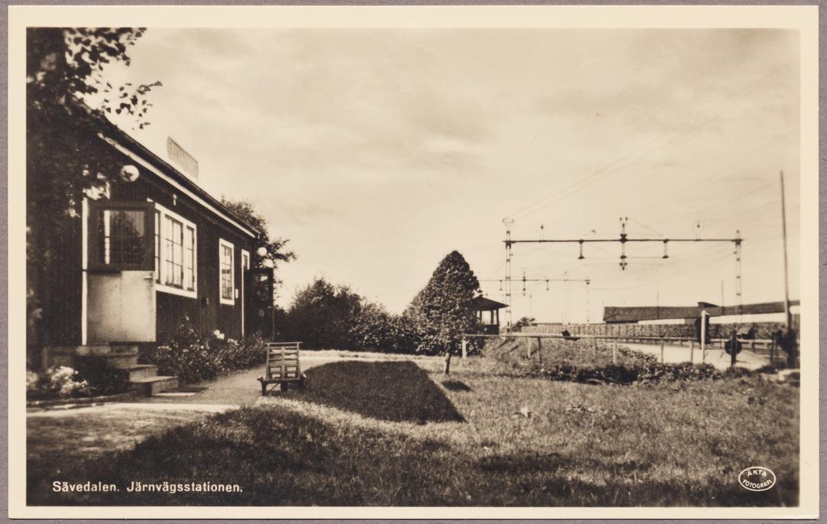 Stationshus med plattform och bangård i bakgrunden.