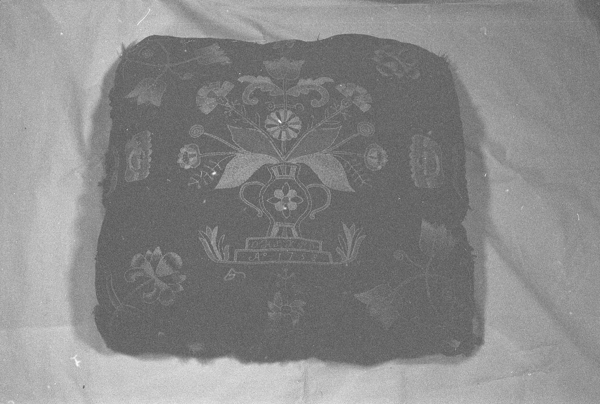 Pute av ull brodert med blomstermotiv og med underside av skinn