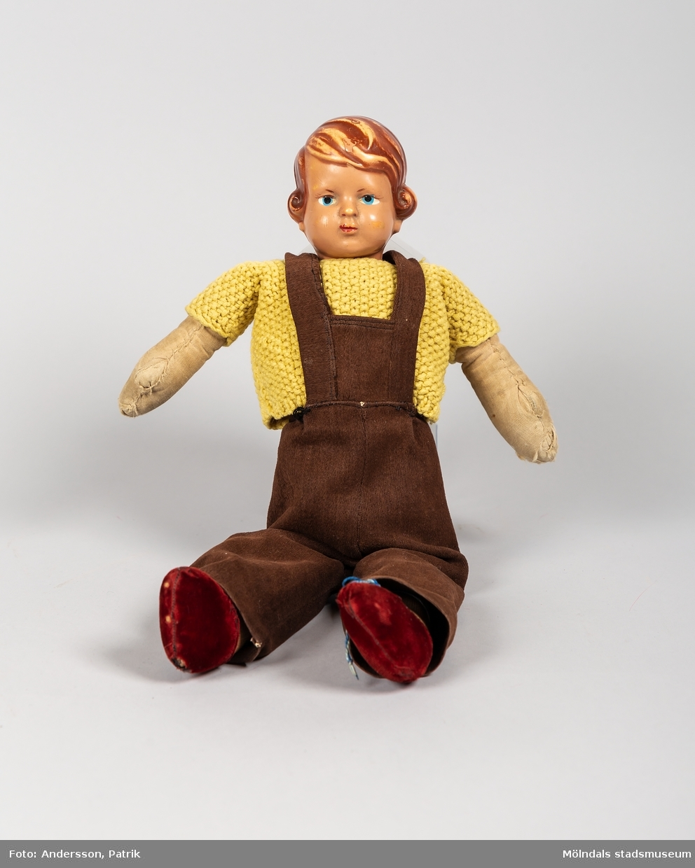 En docka som kallades Lill-Pelle. Dockan är från början av 1950-talet. Rolf som bodde på en lantgård utanför Trelleborg, fick dockan när han var cirka 3-5 år. Dockans kropp och kläder är handsydda av hans moster Elsa som var född 1921. Lill-Pelles gula tröja är stickad av Rolfs syster Gun född 1947, då hon var i 10-årsåldern.