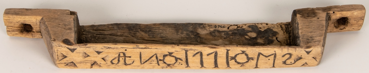 Kat.kort: Hylla, skuren ur ett trästycke, omålad. Eventuellt använd för flinta, stål och fnöske. Märkt i plattskärning. (se skiss på kat.kortet) Acc.kat. Hylla. Trä. Snidat mönster. Märkt: AN 1771 M2.