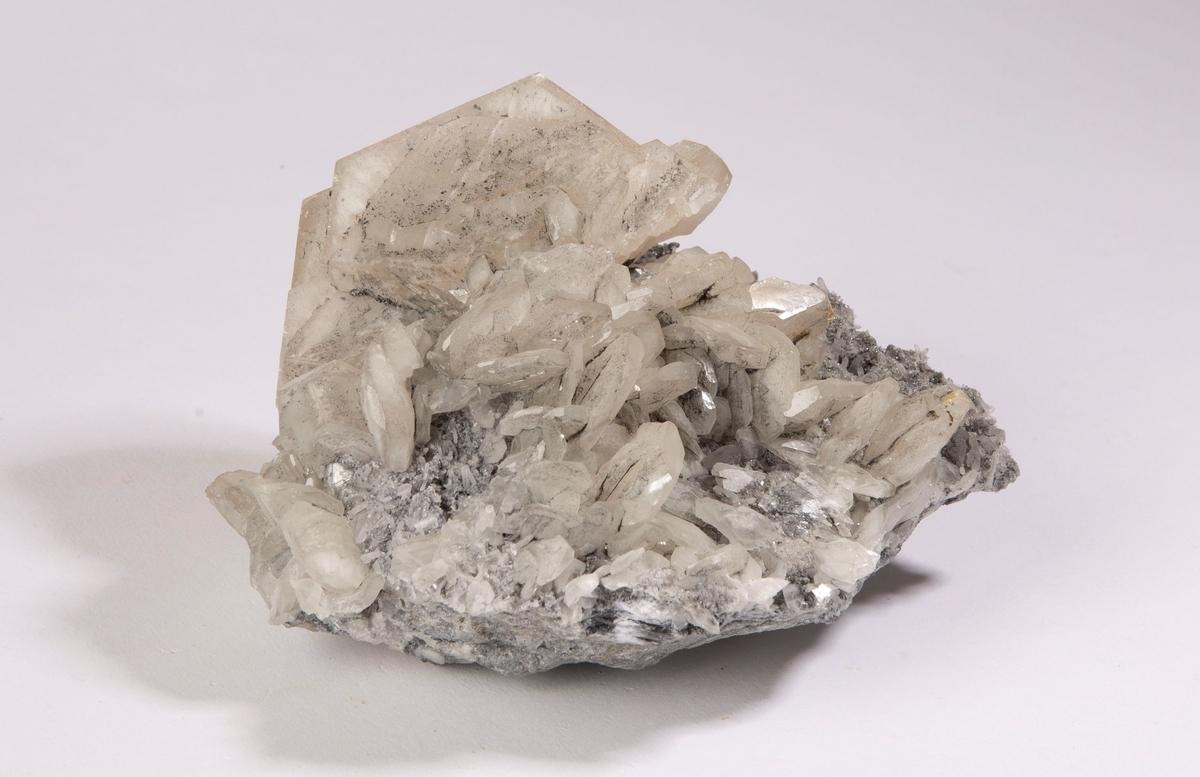 Aggregat med diskosformede krystaller av kalsitt; de største er 5 cm i diameter. Kalsitt har vokst på en matriks av små krystaller av kvarts og grønn og fiolett flusspat. Mildigkeit Gottes gruve, 84 m.