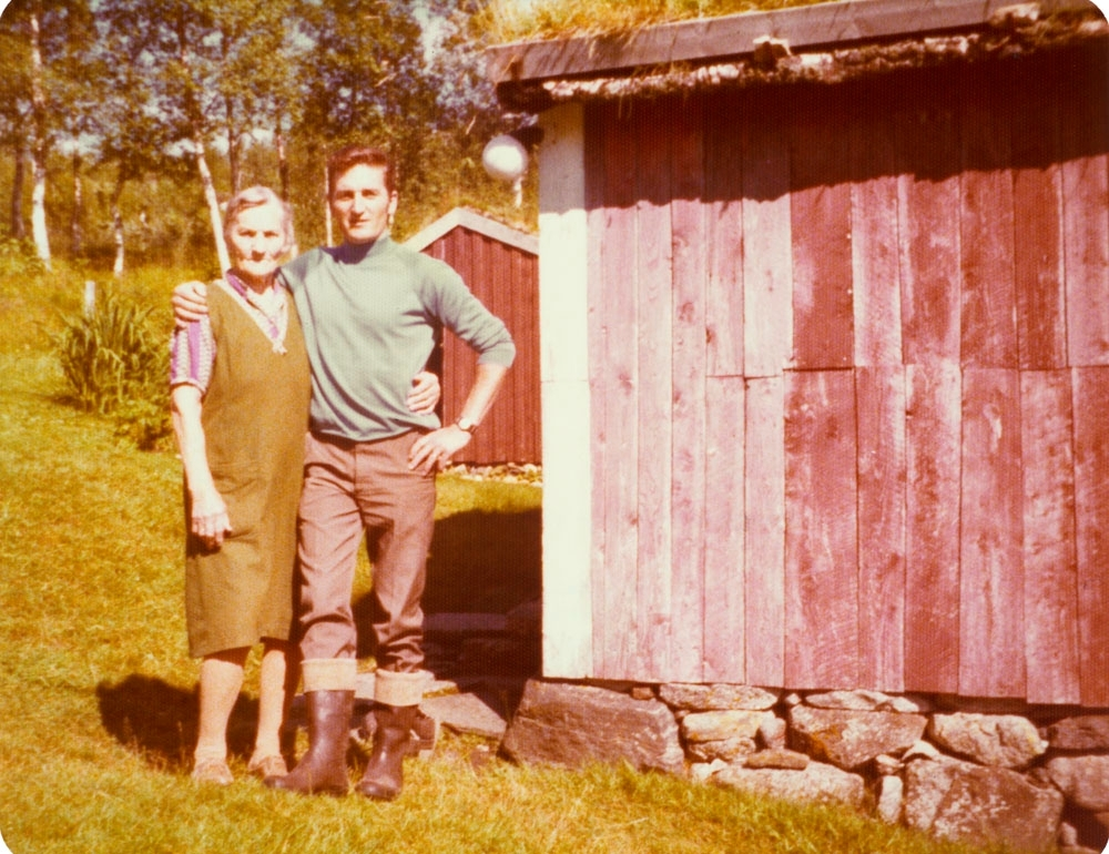 Leirfjord, Vatne, Bjønnhålo. Malla Vatne (f. Hjartland) med barnebarnet Svein Johansen. Malla var født i Vatne og var siste fastboende i Bjønnhålo. Huset på bildet er bolighuset i Bjønnhålo (bislaget). Huset bak er uthuset.
