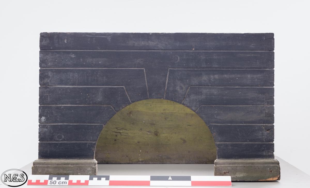 Firkantet ovnskrakk i heltre. De fire sidene er festet sammen ved hjelp av svalehaleskjøt i hjørnene. tre av sidene har innskåret et symetrisk mønster i overflaten - arkitektoniske element. Fronten på ovnskrakken har en rundbuet åpning. Ovnskrakken avsluttes med en profilert sokkel mot bakken.