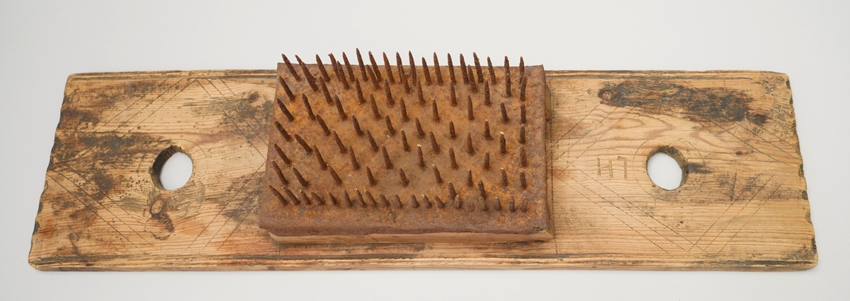 Hekle. Rektangelforma jarn plate med spisse jarnpiggar (18 x 7 piggar i ei råme, men inni råma i diagonale rekkjer) spikra til ei treplate i same storleik. Denne plata er spikra vidare ned i treklossar på kvar langside, slik at det er luft under. Treklossane er feste med to jarnklampar (slått inn frå undersida) til ei trefjøl. Trefjøla har eit sirkelforma hol i kvar ende. Det er rissa inn ein sirkel rundt kvart hol, og streker elles på fjøla, som dekor. Langsidane på fjøla er profilerte heile vegen. Kortsidene har halvsirkelforma fordjupningar som bord langs kanten.