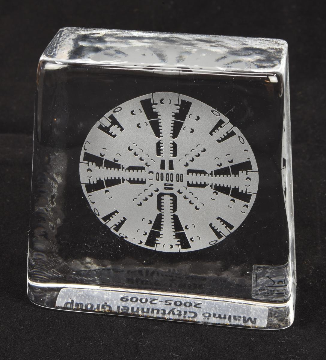 En rektangulär stående minnesplakett i glas med gravyr. Med tillhörande kartongförpackning.  Minnesplakettens (:1) sidor sluttar svagt inåt. På dess baksida finns en gravyr som föreställer framsidan på en tunnelborrmaskin. På plakettens undersida finns en påklistrad genomskinlig plastremsa med svart text. På baksidan finns också en påklistrad genomkinlig plastremsa med tillverkarens märkning.  Förpackningen är formad som en kub och är vit på sidorna med mönster som utgörs av grå streck. På framsidan finns en rött glas och företagets logotyp. Två skumgummibitar i förpackningen håller glasföremålet på plats.
