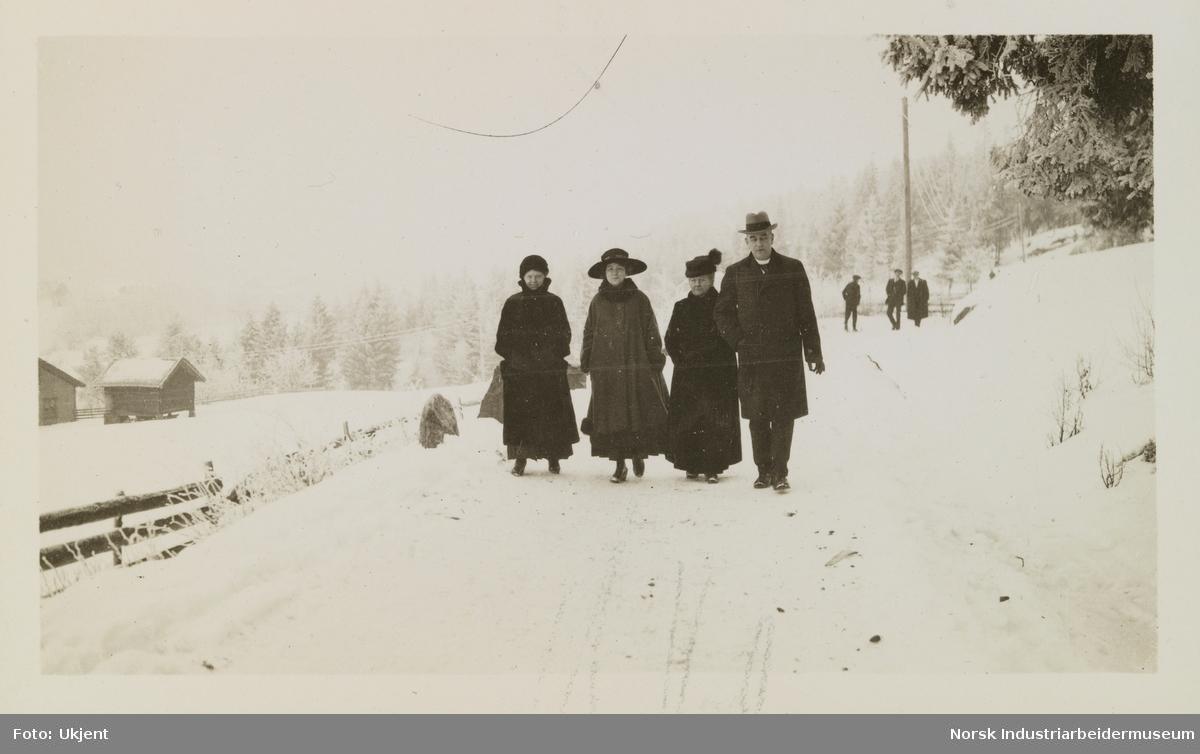 Mennesker går langs snødekt vei