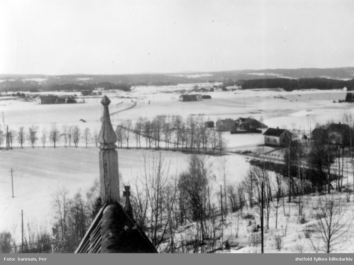 Kirkebygda i vinterdrakt sett fra klokketårnet i Trøgstad kirke ca. 1950.