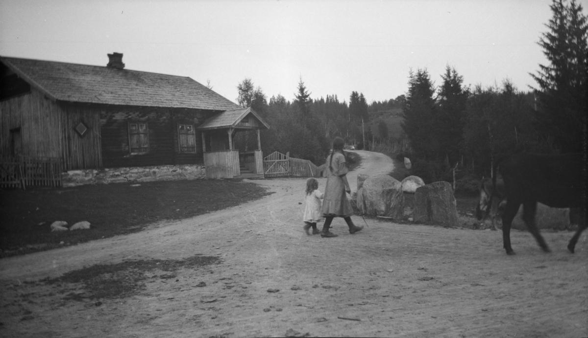 Hus langs landevegen - skilt over inngangspartiet - to jenter på vegen