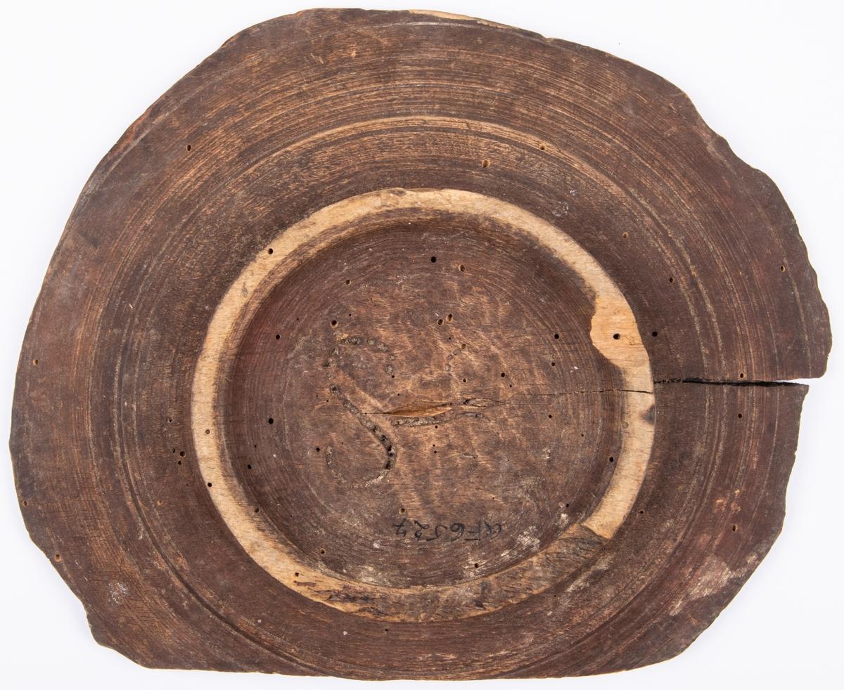 Uppläggnignsfat av trä med såskopp i mitten. Svarvat, defekt, på låg fot. Omålat. Undertill med sylstick märkt; S.
