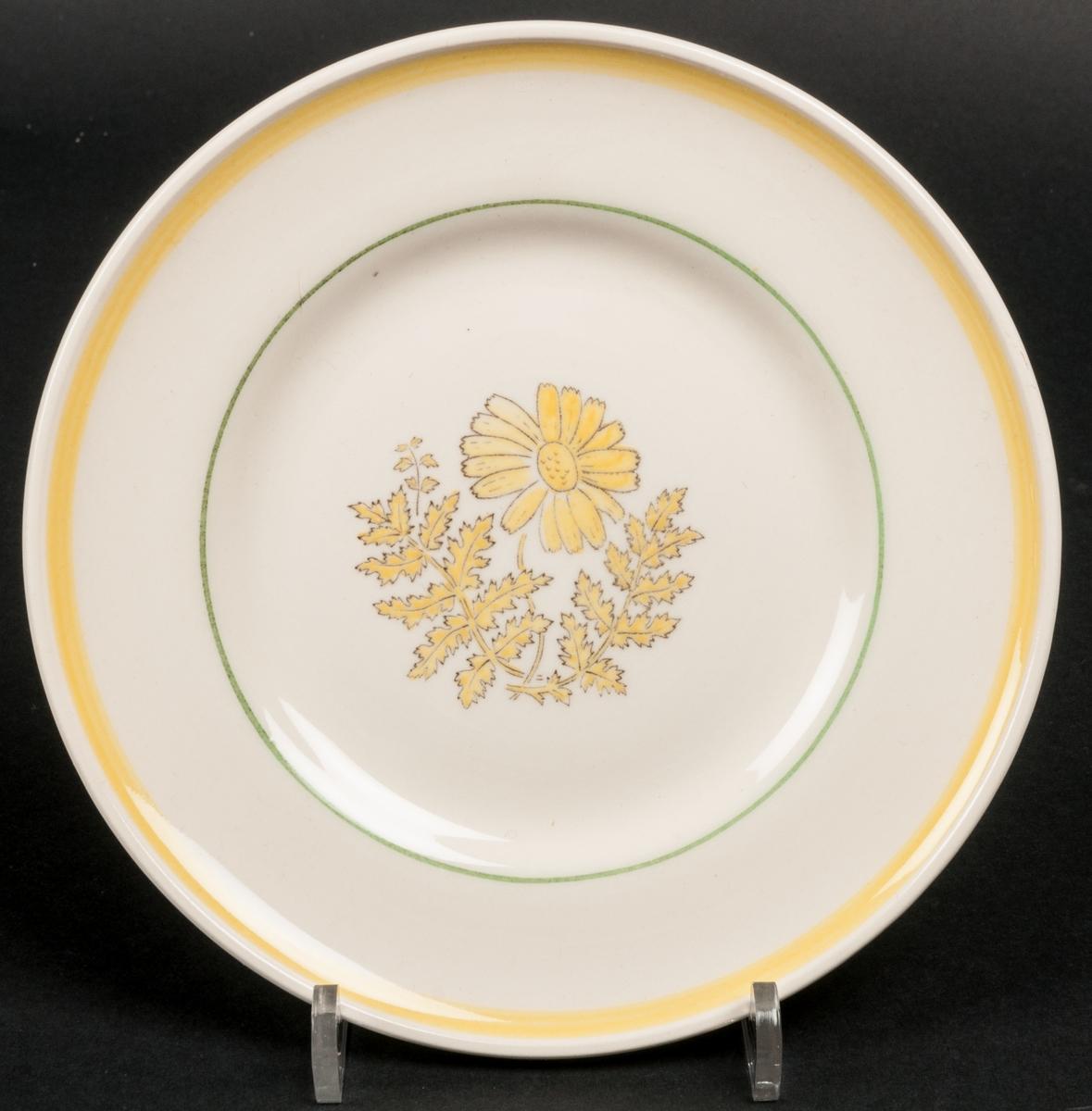Assiett dekor Pyretrum. Koppargravyr med lavering i gult och grönt. Dekoren föreställer en prästkrage eller liknande blomma. Gult band längs yttre delen av brämet och ett smalare grönt band på inre delen.
