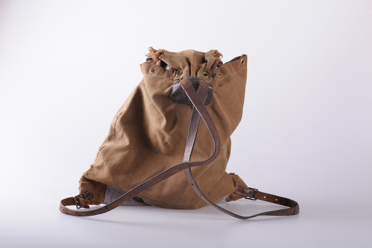 Sekken er laget av brunt lerretsstoff og har brune lærreimer. Lappet i bunnen med grållla stoff. Metallkledde stansede hull øverst ved åpningen til snorgang, og ved en lærkantet splitt under lokket.