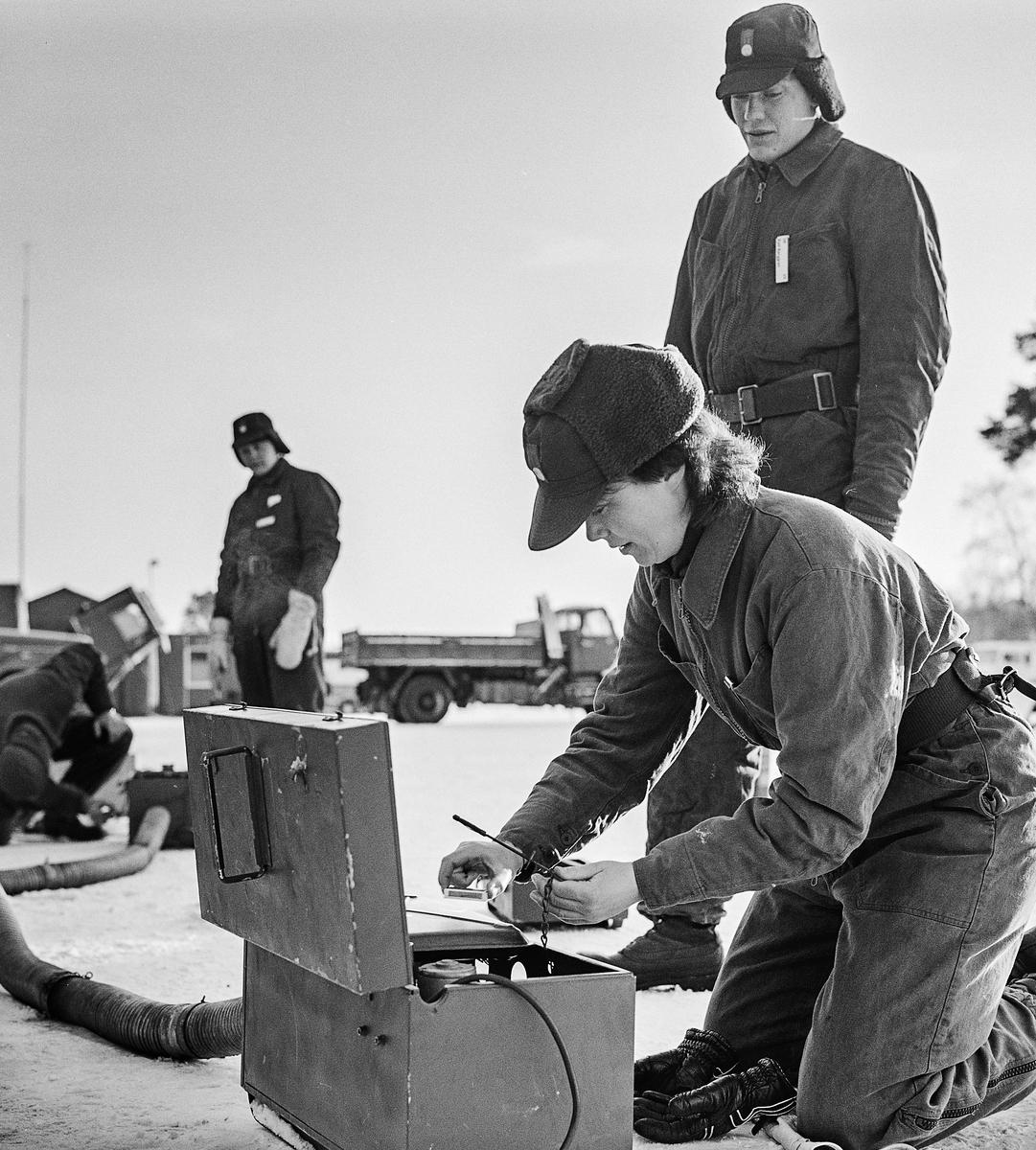 """Trängens aspirantskola vid T 2 i Skövde genomför vinterutbildning i motortjänst.  Värmeaggregat 311 A eldades med bensin och fläkten drevs med ett bilbatteri. Många var rädda för 311:an och """"bensinbomben"""" hade nog många hört talas om. Här fick eleverna lära sig hur man fyller på bensin, kollar tätheten och rätt förfarande vid tändning -- så förhoppningsvis ökade förtroendet.  OBS! två bilder."""