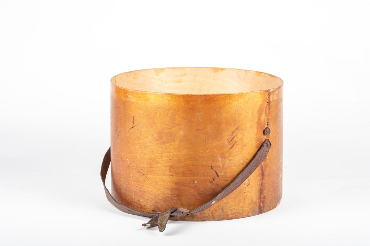 Eske i sylinderform. Den er av finér og er limt i skjøten. Bunnplaten er limt på. En bred lærrem er skrudd fast til esken. Over disse festene er en liten lærbit spikret fast, som tyder på at det har sittet noe der som er revet av. Lærremmen har nagler og består egentlig av to remmer som er tredd i hverandre og knyttet.