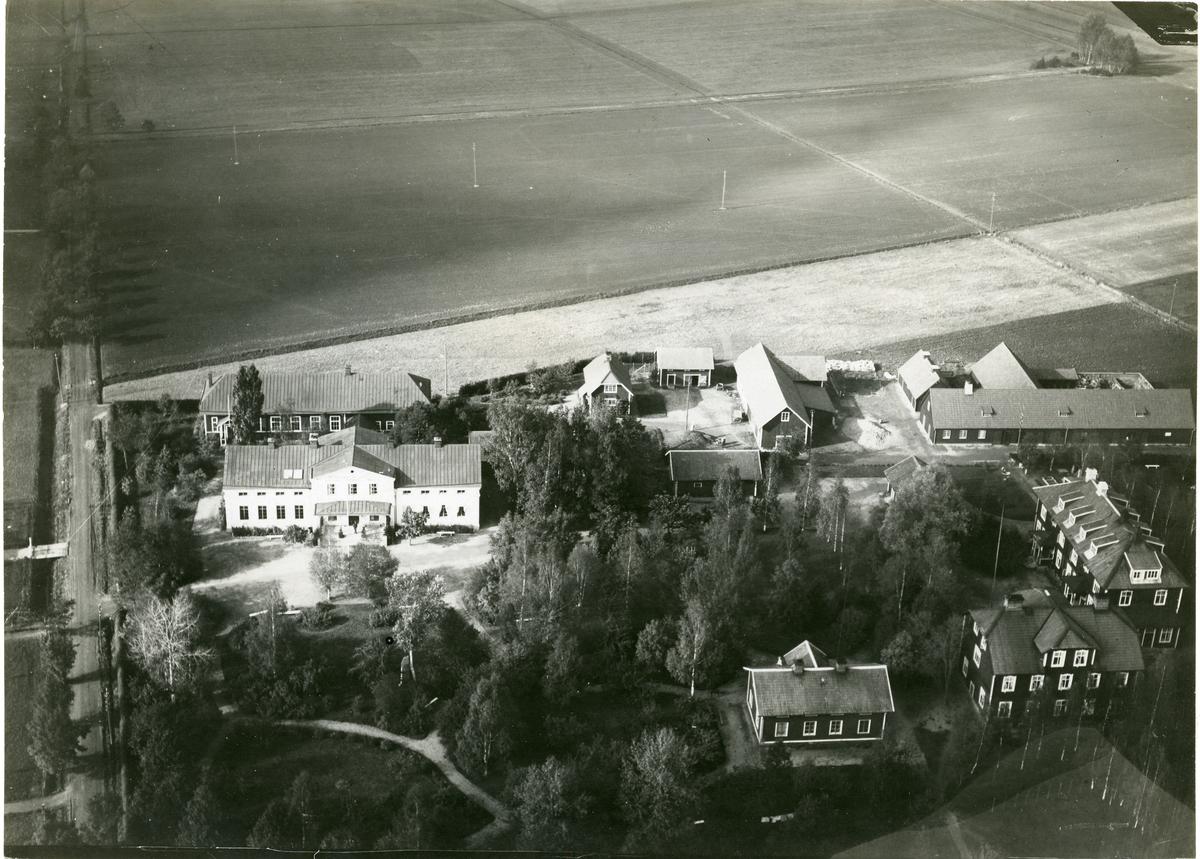 Sala kn, Kumla sn. Flygfoto över Tärna folkhögskola, Kumla kyrkby, med omkringliggande lantbruk.