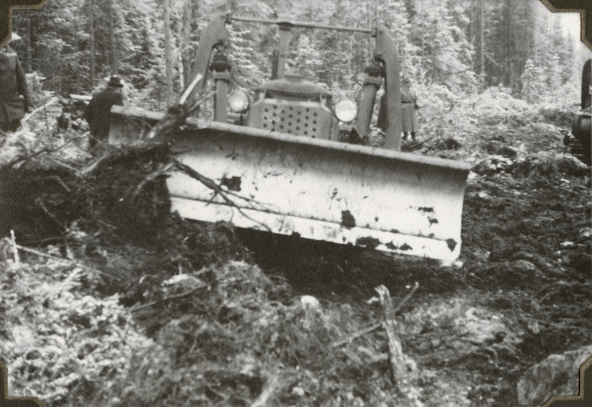 """Text i fotoalbum: """"Brytning av timmerbasväg med ingbat traktorer nov 1941, Dala-Floda skogar. """""""