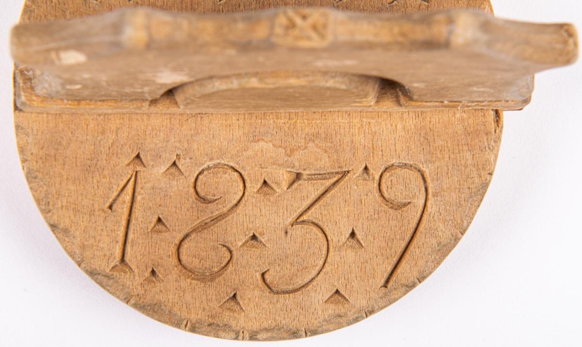 """Smörstämpel, skuren i björk. Cirkelrund bricka med vinkelrätt monterat handtag gjort i två delar. Märkt på ovansidan: """"A:A:D"""" och: """"1:8:3:9""""."""