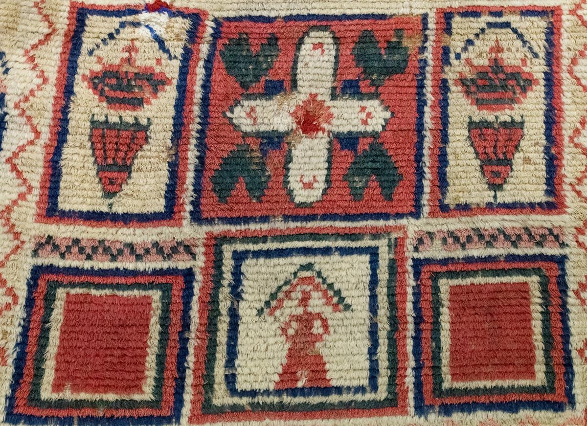 Brudrya, gjord i en våd. Bottenväven rips över 2 varptrådar. Varp och inslag är av lin, flossan av ull. Geometriska och rektangulära mönster i fält. Överst fält med svart botten , blomlika figurer, sicksack linje utmed kanten. Nedanför ett rött mittfält med likarmat kors med avfasade korsändar och på sidorna två vita fält med blomställningar. Nederst ett mittfält vitt med röd människofigur medsvart vinkel över, samt bredvid två röda fält utan figurer. däromkring smal vit bård med röd sicksack linje och utanför denna en bred bård med sicksack band.