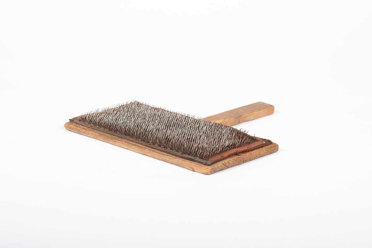 Karden består hver av et trestykke med innfelt håndtak og med lærstykke fulle av små metallstenger som er festet til trestykket.