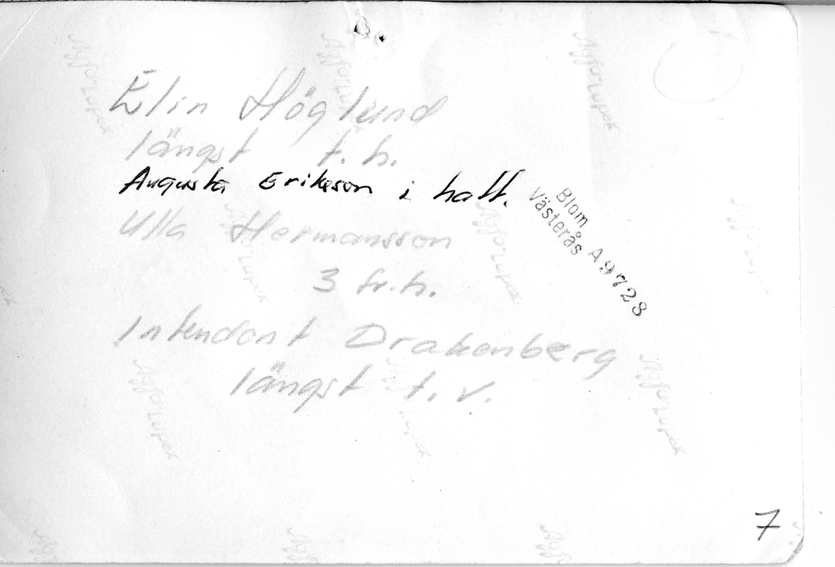Baksidan på foto föreställande picknick i samband med Arbogautställningen 1935. Handskriven text om vilka personer som är med i gröngräset. Elin Höglund sitter längst till höger. Framsidan AKF-14501