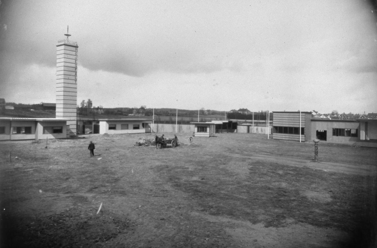 Vy över utställningsområdet som håller på att ställas iordning. Några män plockar upp bräder på en kärra dragen av en häst. Reklamobelisken är färdigställd. I bakgrunden, strax till höger om mitten, ses en byggnad med tre skorstenar. Det är gården Nyby norr, personalbostäder till Arboga Glasbruk.