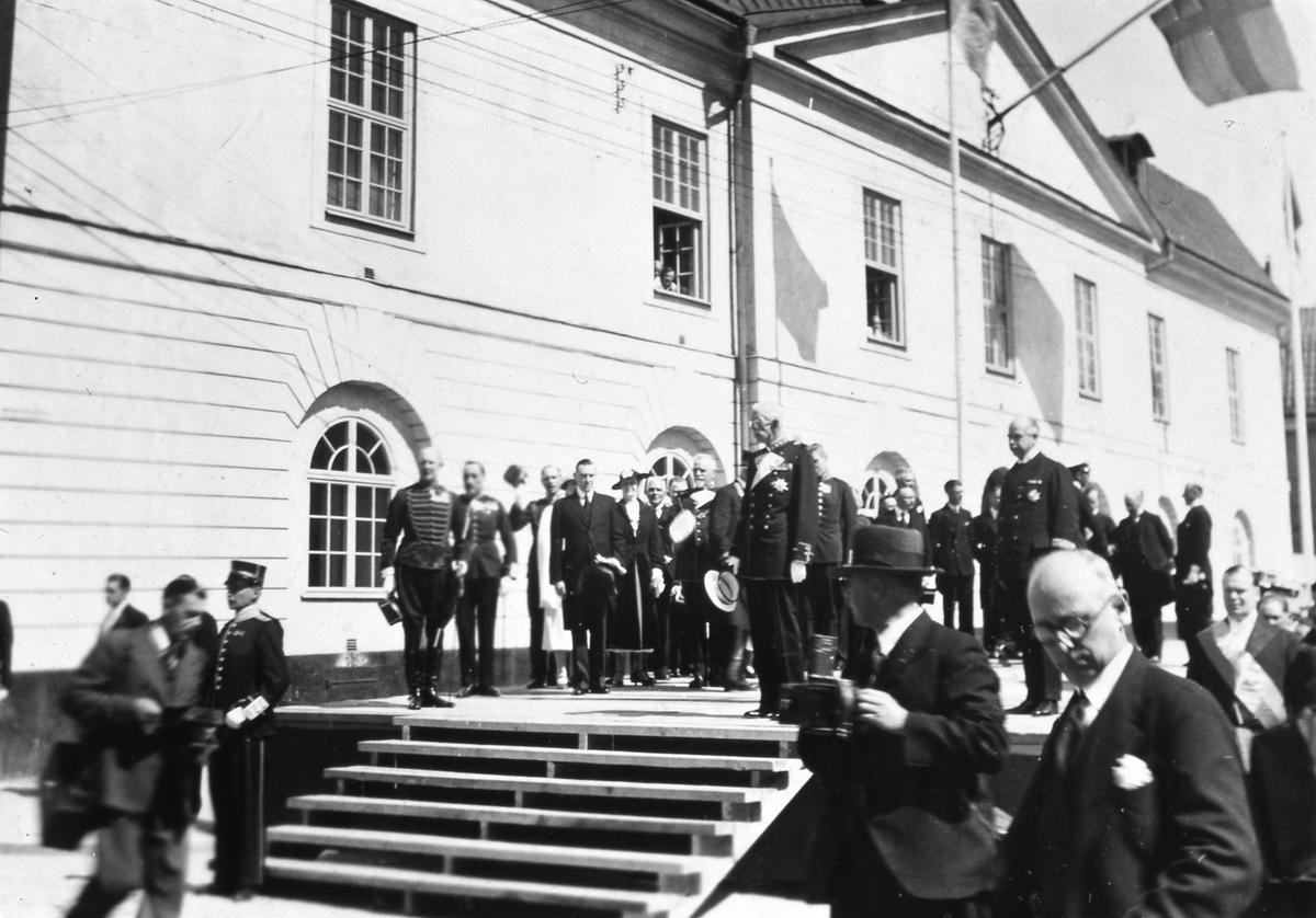 Kung Gustaf V står på scenen framför Rådhuset tillsammans med högtidsklädda män och kvinnor. Några bär uniform. Flaggorna är hissade. I Arboga firas Riksdagens 500-årsjubileum. Arbogautställningen pågår samtidigt.