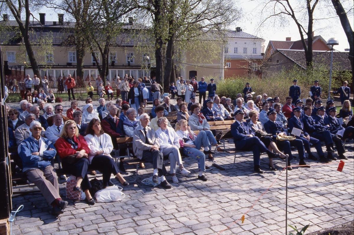 Bland publiken, i Olof Ahllöfs park, sitter medlemmarna i en blåsorkester och väntar på att få äntra scenen. I bakgrunden skymtar Stadskällaren.