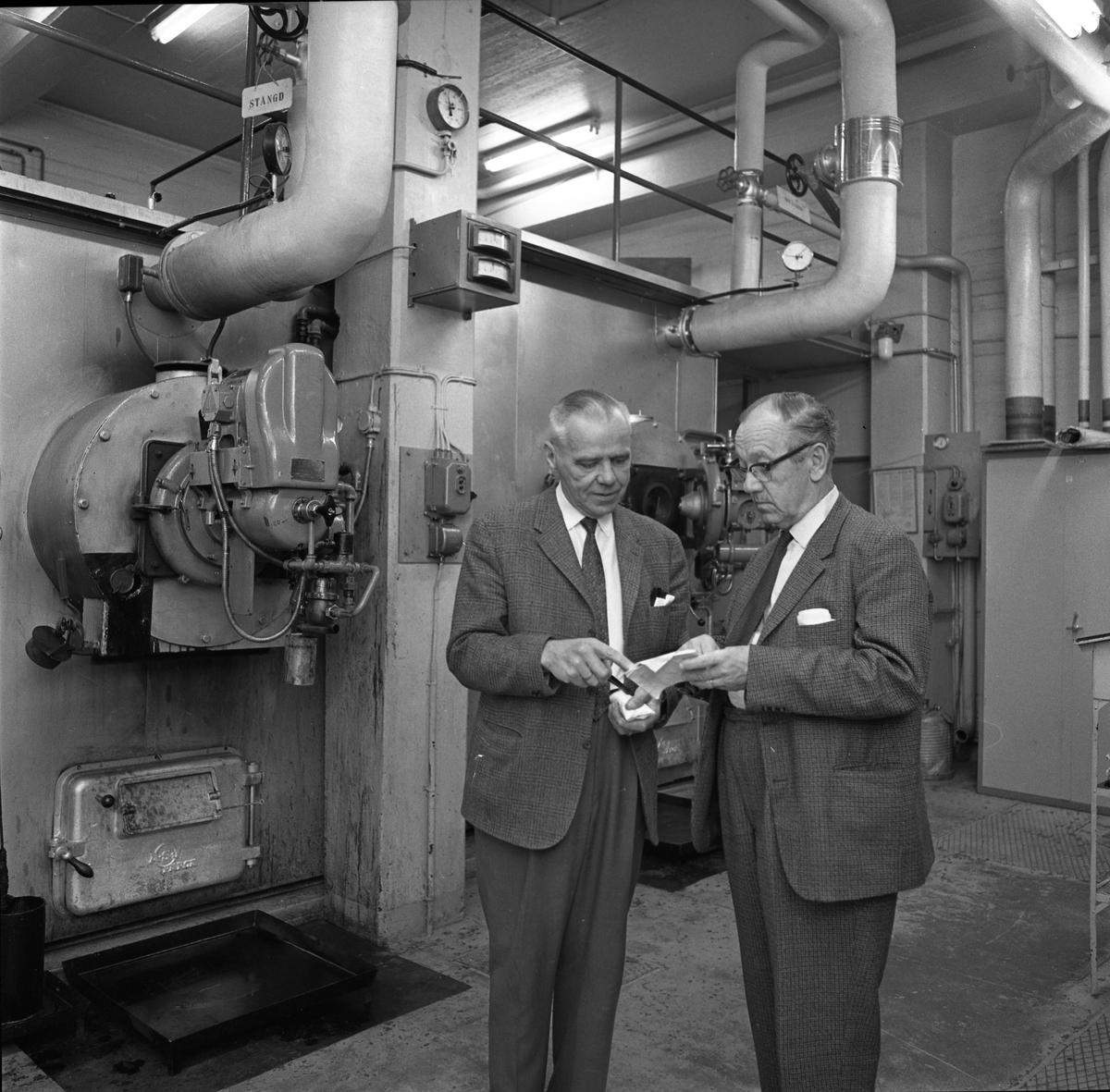Alf Hedlund, maskinmästare på Centrala Verkstaden Arboga  Två kostymklädda män som befinner sig i industrimiljö