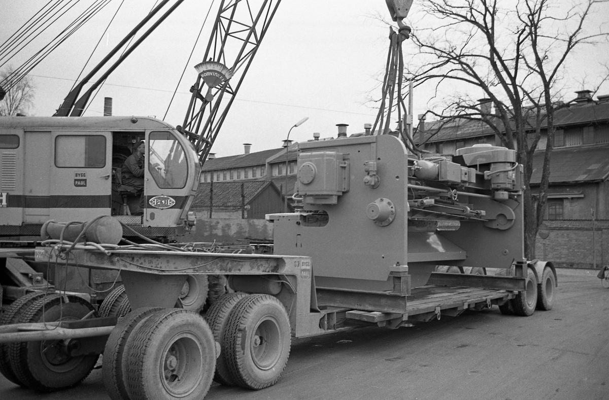 """En lyftkran flyttar en gradsax som ska transporteras med järnväg. Gradsaxen är tillverkad på """"Meken"""", Arboga Mekaniska Verkstad.  En man i en lyftkran lastar en stor maskin på ett släp."""